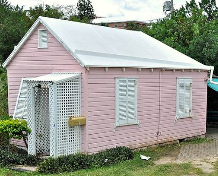 In this image is a pink she shed reused from an old shed with a pink pastel finish