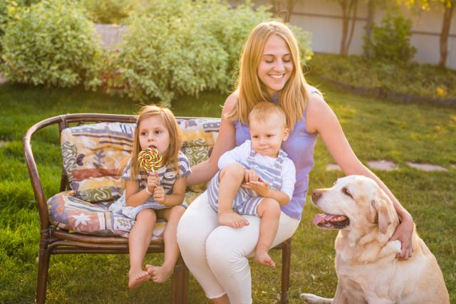 Mother, children and dog relaxing in the garden